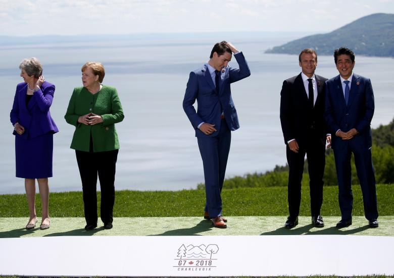 British Prime Minister Theresa May, German Chancellor Angela Merkel, Canada's Prime Minister Justin Trudeau, France's President Emmanuel Macron and Japanese Prime Minister Shinzo Abe wait for U.S. President Donald Trump to join them for a family photo at the G7 Summit in Charlevoix, Quebec, Canada, June 8.