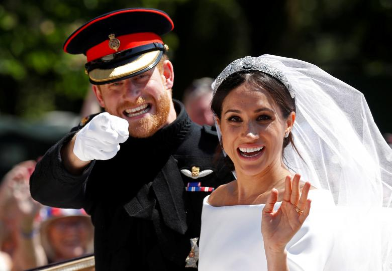 Britain's Prince Harry gestures next to his wife Meghan as they ride a horse-drawn carriage after their wedding ceremony at St George's Chapel in Windsor Castle, May 19.