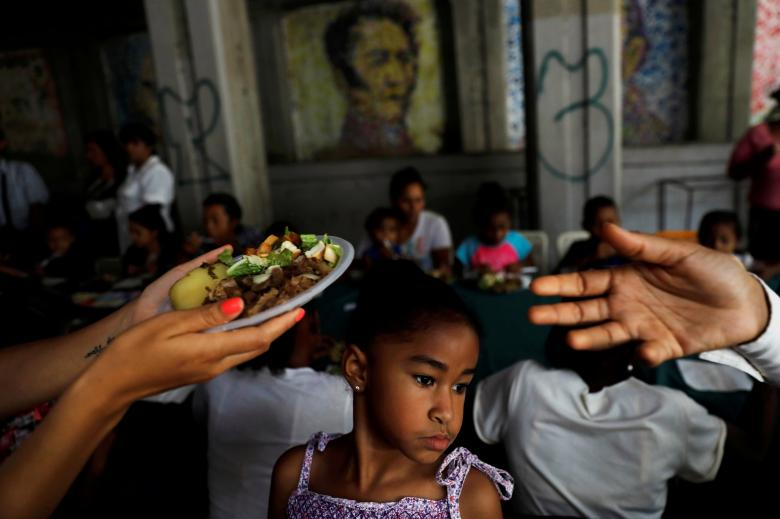 A child looks on, as volunteers of Venezuelan presidential candidate Javier Bertucci of the Esperanza por el Cambio party give food plates to women and children as part of a Mother's Day celebration, during a campaign rally in Caracas, Venezuela, May 13.