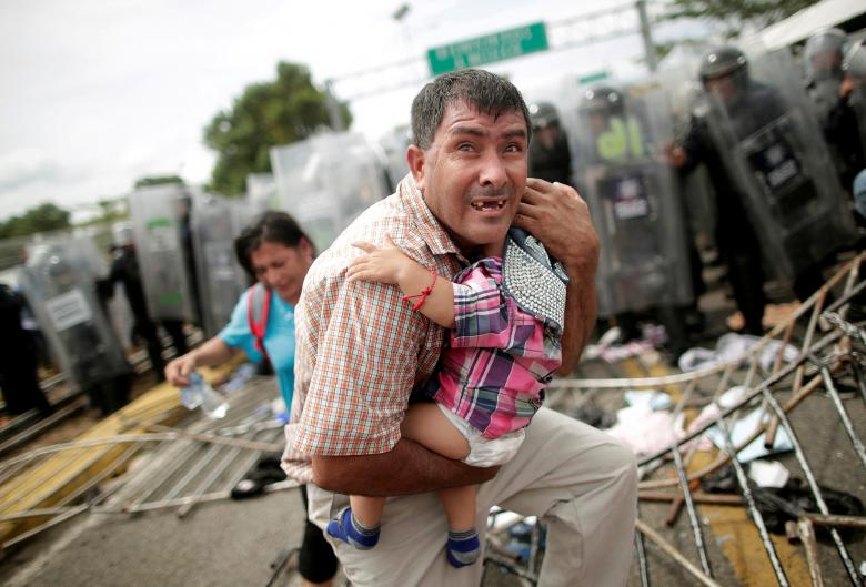 A Honduran migrant protects his child after fellow migrants, part of a caravan trying to reach the U.S., stormed a border checkpoint in Guatemala, in Ciudad Hidalgo, Mexico, October 19.