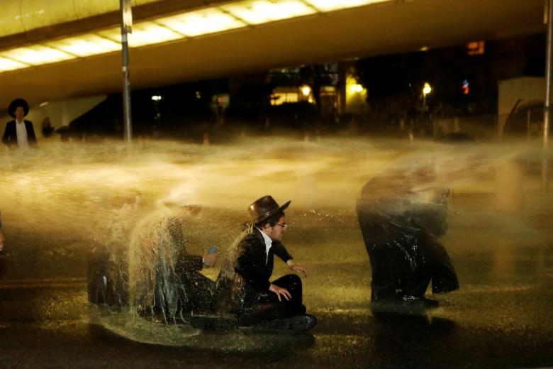 Israeli ultra-Orthodox Jewish men sit as a water cannon is activated during a protest against the detention of a member of their community who refused to serve in the Israeli army, in Jerusalem, March 8.