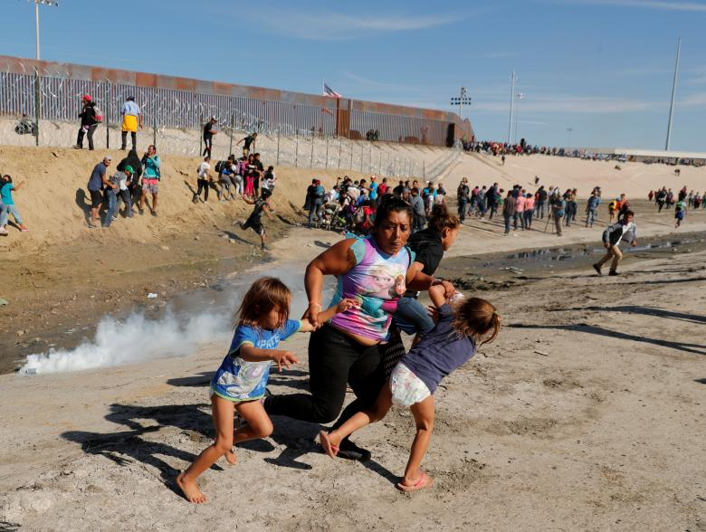 Maria Meza (C), a 40-year-old migrant woman from Honduras, part of a caravan of thousands from Central America trying to reach the United States, runs away from tear gas with her 5-year-old twin daughters Saira Mejia Meza (L) and Cheili Mejia Meza (R) in front of the border wall between the U.S. and Mexico, in Tijuana, Mexico, November 25