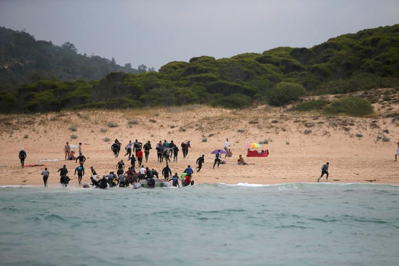 Migrants disembark from a dinghy at Del Canuelo