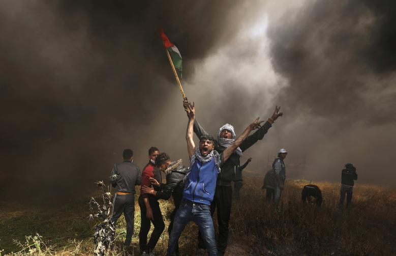 Palestinian demonstrators shout during clashes with Israeli troops at a protest demanding the right to return to their homeland, at the Israel-Gaza border east of Gaza City, April 6.
