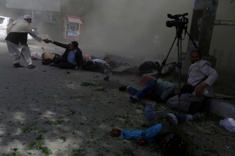 Afghan journalists are seen after a second blast in Kabul, Afghanistan, April 30. The explosion killed nine reporters, photographers and cameramen covering the attack.