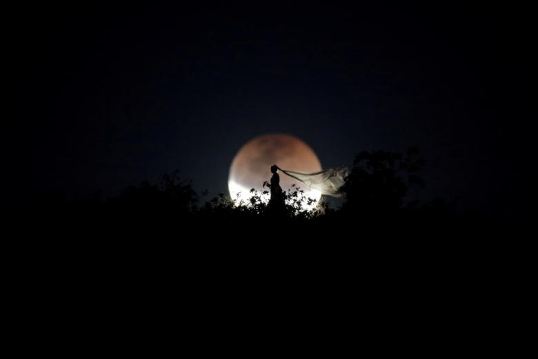 A bride poses for photo during a total lunar eclipse in Brasilia, Brazil, July 27.