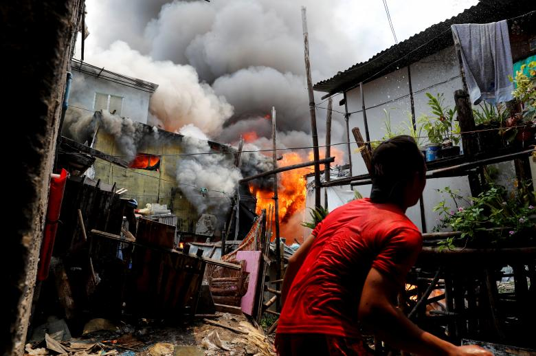 A resident throws water at his house on fire at a residential neighborhood of an informal settlement, in Muntinlupa, Metro Manila, Philippines, June 4.