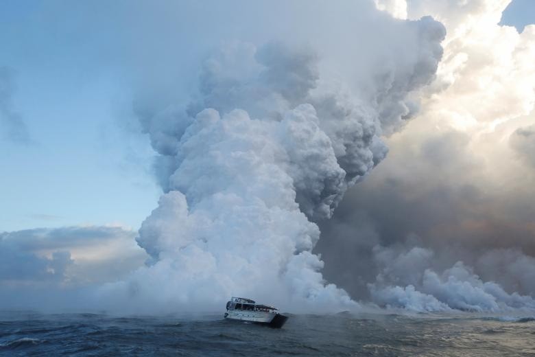 People watch from a tour boat as lava flows into the Pacific Ocean in the Kapoho area, east of Pahoa, during ongoing eruptions of the Kilauea Volcano in Hawaii, June 4.