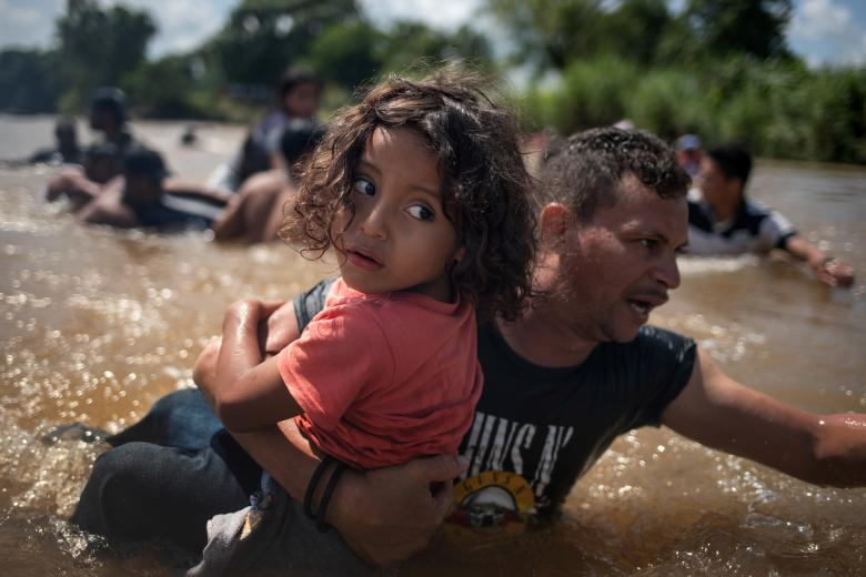 Luis Acosta holds 5-year-old Angel Jesus, both from Honduras, as a caravan of migrants from Central America en route to the United States crossed through the Suchiate River into Mexico from Guatemala in Ciudad Hidalgo, Mexico, October 29.