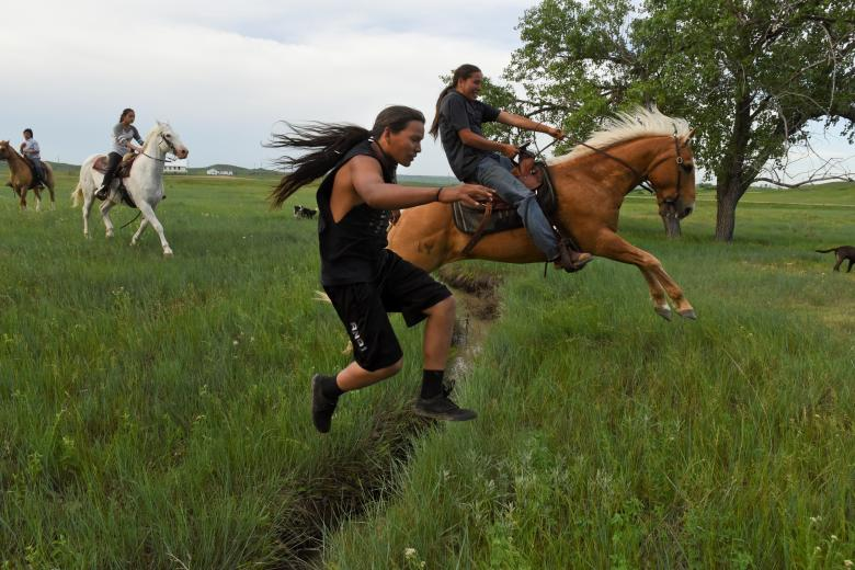 Mahto In The Woods jumps over a small creek on foot while his cousin Jayden Lookinghorse jumps over on his horse on the Cheyenne River Reservation in Green Grass, South Dakota, May 31.