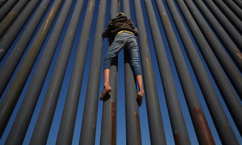 A migrant, part of a caravan of thousands from Central America trying to reach the United States, climbs the border fence between Mexico and the United States, in Tijuana, Mexico, November 18.