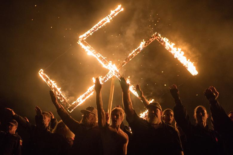 Supporters of the National Socialist Movement, a white nationalist group based in the U.S., give Nazi salutes while taking part in a swastika burning at an undisclosed location in Georgia, April 21.