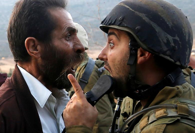 A Palestinian man argues with an Israeli soldier during clashes over an Israeli order to shut down a Palestinian school near Nablus, in the occupied West Bank, October 15.