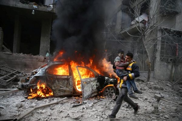 A Syria Civil Defence member carries a wounded child in the besieged town of Hamoria, Eastern Ghouta, in Damascus, Syria, January 6.