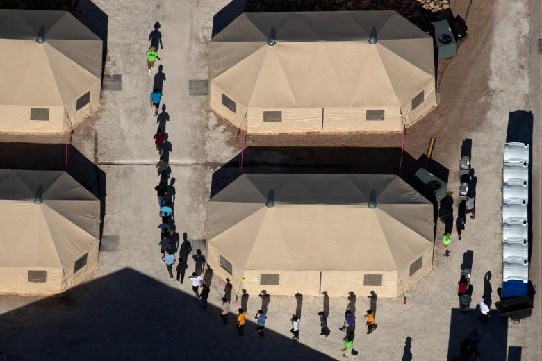 Immigrant children are led by staff in single file between tents at a detention facility next to the Mexican border in Tornillo, Texas, June 18.