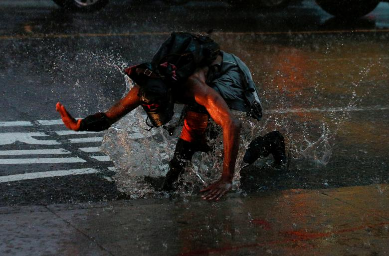 A man splashes in a puddle in Times Square during a heavy midday downpour in New York, July 17.